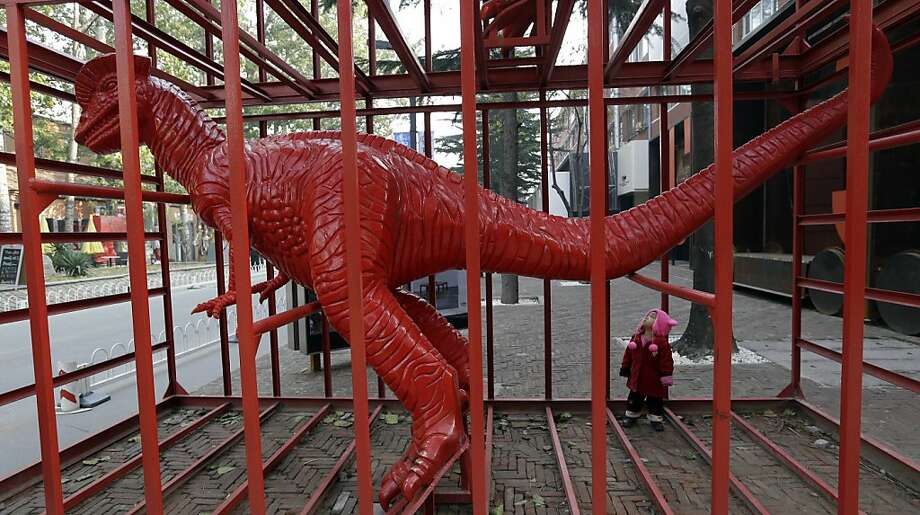 A child looks at a dinosaur sculpture designed by Chinese artist Sui Jianguo at the 798 Art District in Beijing Wednesday, Nov. 21, 2012. The 798 Art District, often compared to New York City's Greenwich Village, is a thriving community of about 400 galleries, shops and restaurants on the eastern edge of Beijing housed in a complex of former electronics factories built with the help of East Germany in the 1950s. Photo: Lee Jin-man, Associated Press
