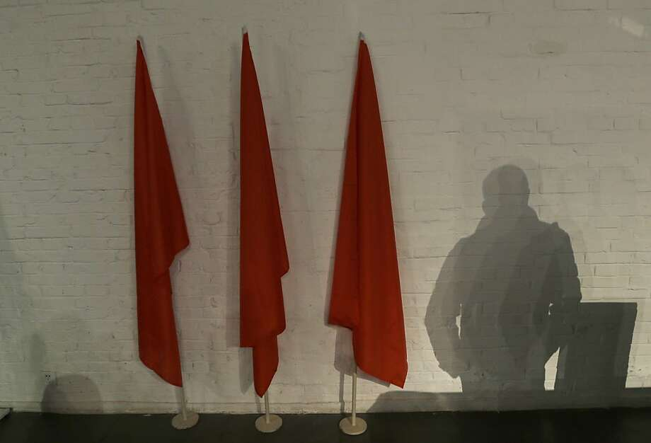 A shadow of a man is cast next to red flags at the 798 Art District in Beijing, China, Wednesday, Nov. 21, 2012. The 798 Art Dstrict, often compared to New York City's Greenwich Village, is a thriving community of about 400 galleries, shops and restaurants on the eastern edge of Beijing housed in a complex of former electronics factories built with the help of East Germany in the 1950s. Photo: Lee Jin-man, Associated Press