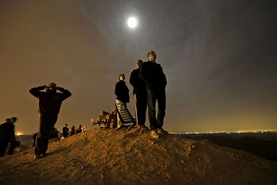 The moon illuminates Israelis standing on a hill at the Israeli town of Sderot, overlooking the Gaza Strip, background right, as they watch a missile, not seen, fired by Palestinian militants from inside Gaza towards southern Israel, Wednesday, Nov. 21, 2012, shortly before a cease-fire is announced between Israel and Hamas. Israel and the Hamas militant group agreed to a cease-fire Wednesday to end eight days of the fiercest fighting in nearly four years, promising to halt attacks on each other and ease an Israeli blockade constricting the Gaza Strip.The deal was brokered by the new Islamist government of Egypt, solidifying its role as a leader in the quickly shifting Middle East after two days of intense shuttle diplomacy that saw U.S. Secretary of State Hillary Rodham Clinton race to the region. Photo: Lefteris Pitarakis, Associated Press