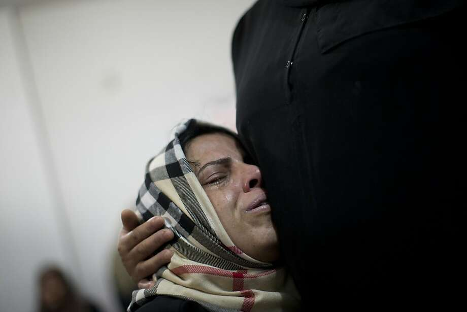 A Palestinian relative cries during the funeral of Mohammed al-Koumi in Gaza City, Wednesday, Nov. 21, 2012. Israeli airstrikes killed three Palestinian journalists in their cars on Tuesday, a Gaza health official and the head of the Hamas-run Al Aqsa TV said. Israel acknowledged targeting the men, claiming they had ties to militants. Photo: Bernat Armangue, Associated Press