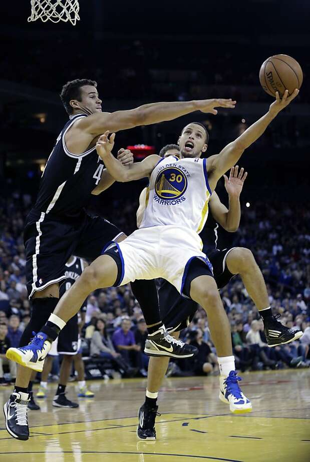 Golden State Warriors' Stephen Curry (30) scores past Kris Humphries, left, during the second half of an NBA basketball game in Oakland, Calif., Wednesday, Nov. 21, 2012. Golden State won 102-93. (AP Photo/Marcio Jose Sanchez) Photo: Marcio Jose Sanchez, Associated Press