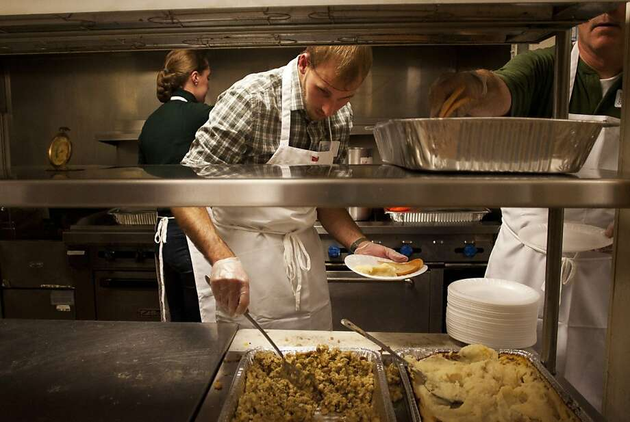 Jason Kramer, center, Stacy Kramer, left and Tom Laarman, right serve the 21st annual Degage Ministries Thanksgiving meal Wednesday, Nov. 21, 2012 at Degage Ministries in Grand Rapids Mich. Photo: Sally Finneran, Associated Press
