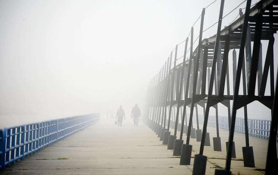 Fisherman walk out onto the St. Joseph, Mich. north pier on Wednesday, Nov. 21, 2012 in spite of the heavy fog that blanketed the area. Photo: Jody Warner, Associated Press