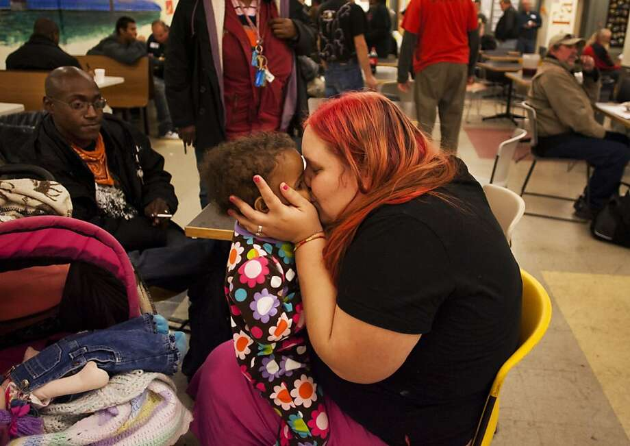 Amber Lyles kisses her daughter Ameriya Crow, 1, while Octavius Crow looks on at the 21st annual Degage Ministries Thanksgiving meal Wednesday, Nov. 21, 2012 at Degage Ministries in Grand Rapids, Mich. Photo: Sally Finneran, Associated Press