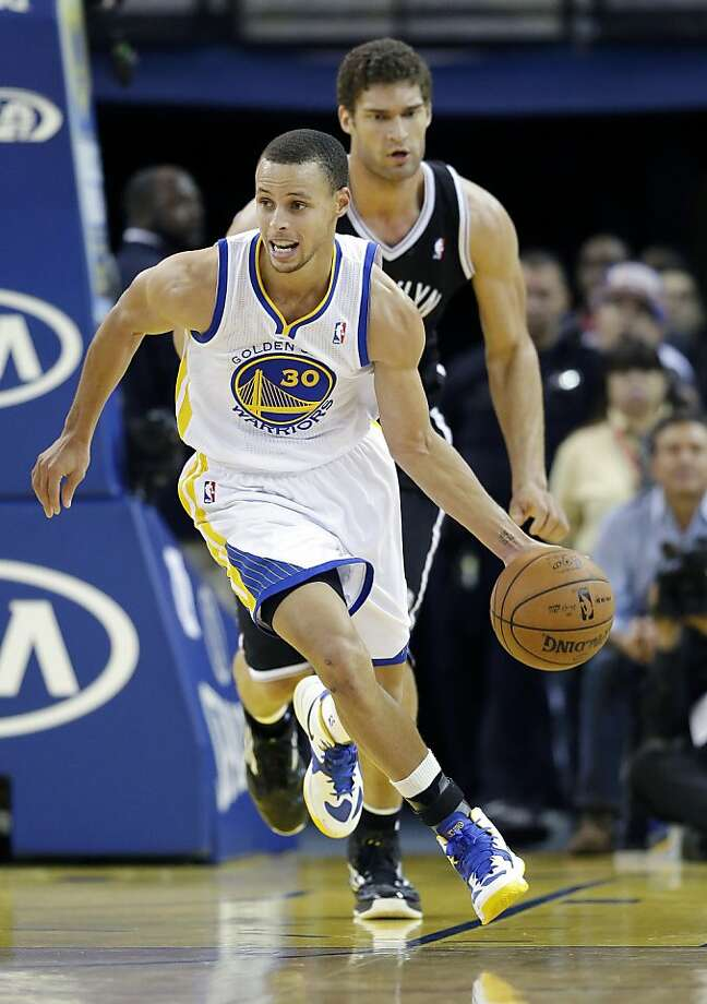 Golden State Warriors' Stephen Curry (30) drives past Brooklyn Nets' Brook Lopez during the second half of an NBA basketball game in Oakland, Calif., Wednesday, Nov. 21, 2012. Golden State won 102-93. (AP Photo/Marcio Jose Sanchez) Photo: Marcio Jose Sanchez, Associated Press