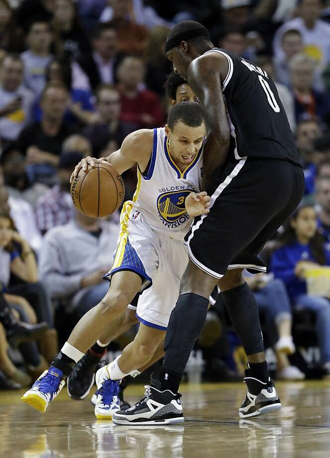 Golden State Warriors' Stephen Curry, left, tries to dribble around Brooklyn Nets' Andray Blatche (0) during the first half of an NBA basketball game in Oakland, Calif., Wednesday, Nov. 21, 2012. (AP Photo/Marcio Jose Sanchez) Photo: Marcio Jose Sanchez, Associated Press
