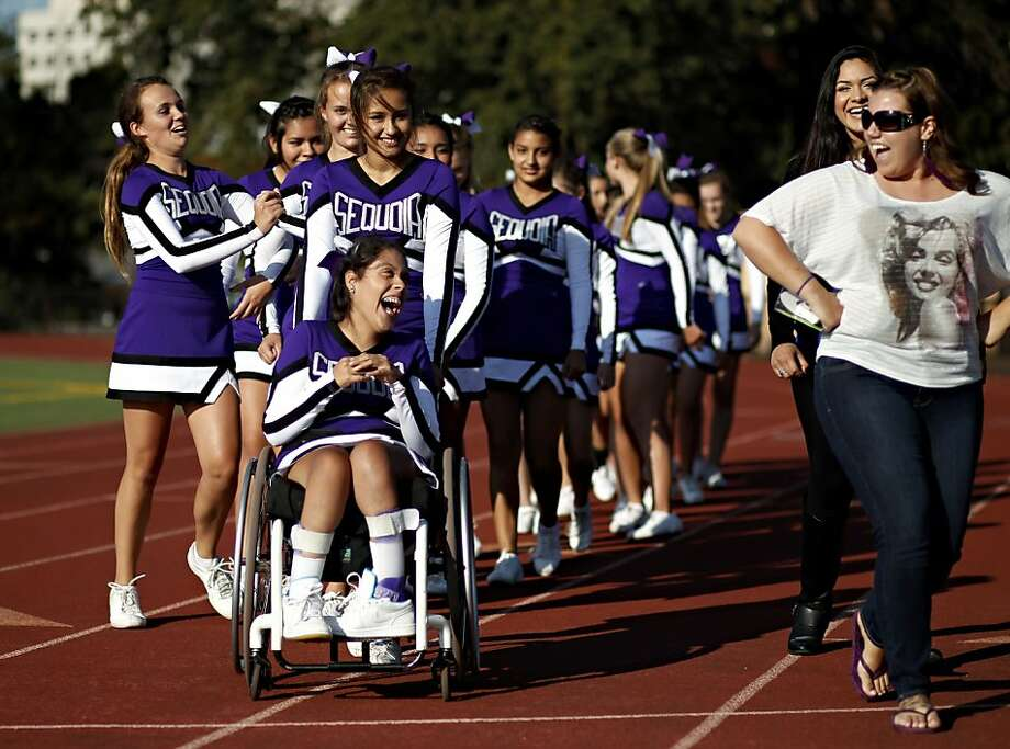 Sequoia High School junior varsity cheerleader Angel Gonzalez-Prado (front) gets a push from Elisa Carrizales while sharing a laugh with coach Stacy Morell (far right) during the junior varsity football game on Friday, September 28, 2012 in Redwood, Calif. Photo: Beck Diefenbach, Special To The Chronicle