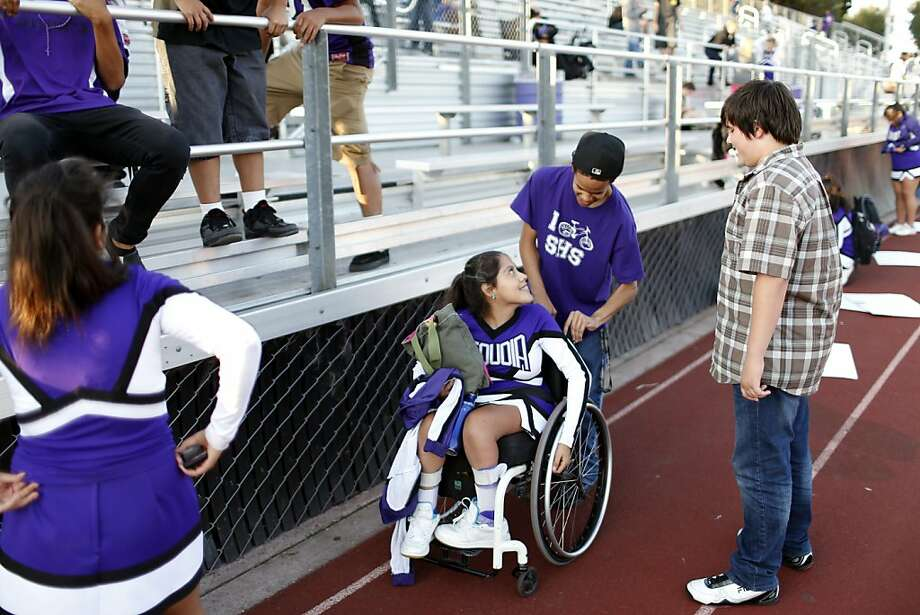 Sequoia High School junior varsity cheerleader Angel Gonzalez-Prado (in wheelchair) is helped by friend Issac Whiting following the junior varsity football game on Friday, September 28, 2012 in Redwood, Calif. Photo: Beck Diefenbach, Special To The Chronicle