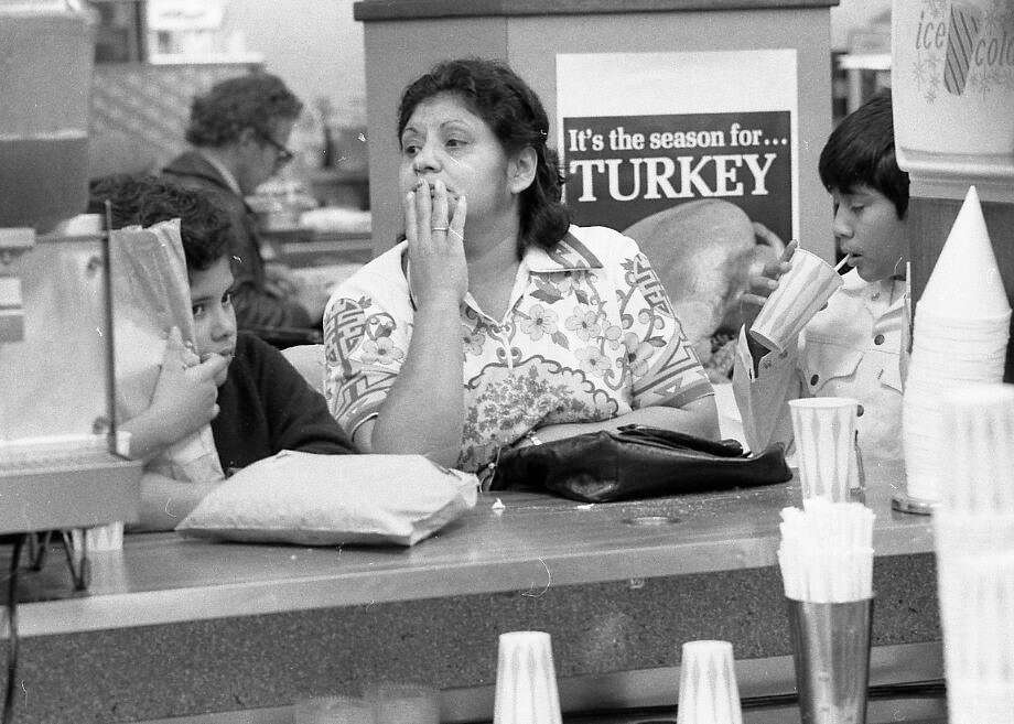 "Nov. 24, 1978: This was in a photo envelope titled ""Thanksgiving Blues Around S.F."" Strangers are ordering food at a diner counter. This woman has a lot on her mind, but the children look healthy. If you can get yourself out the door in San Francisco, then you're not alone on Thanksgiving."