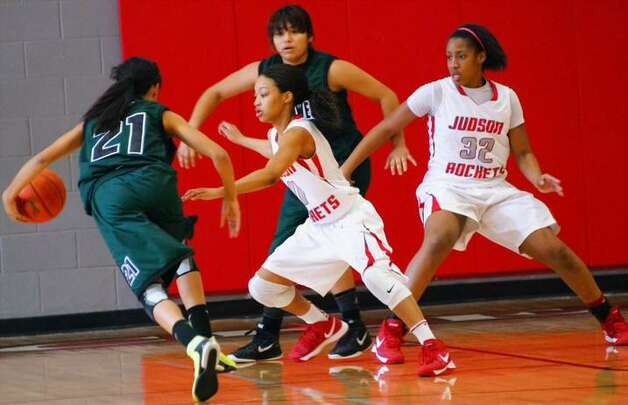 Judson's Simone Fields (32) blocks out underneath while teammate Samantha Allen (11) steps out to guard Southwest Lady Dragons Alexandra Busby during Judson's 73-30 win Friday over the Dragons. Photo: Lavon Brown / For The NE Herald