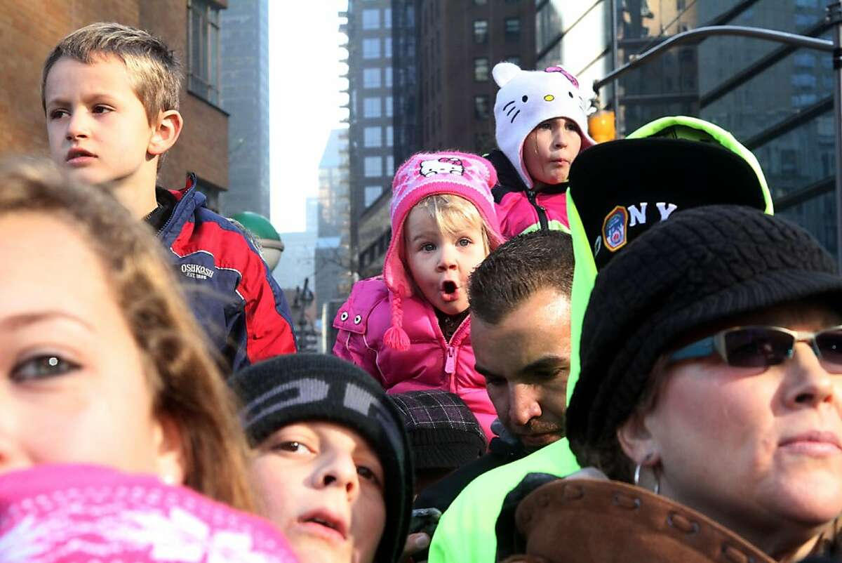 Reagon Long, 3, from Oxford, N.Y, background center, watches the 86th Annual Macy's Thanksgiving Day Parade.