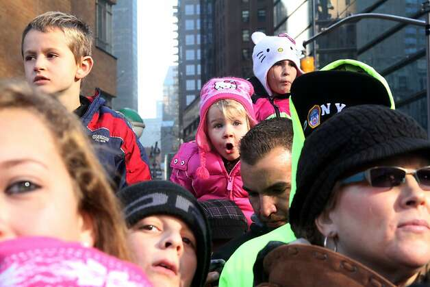 Reagon Long, 3, from Oxford, N.Y, background center, watches the 86th Annual Macy's Thanksgiving Day Parade. Photo: Tina Fineberg, Associated Press