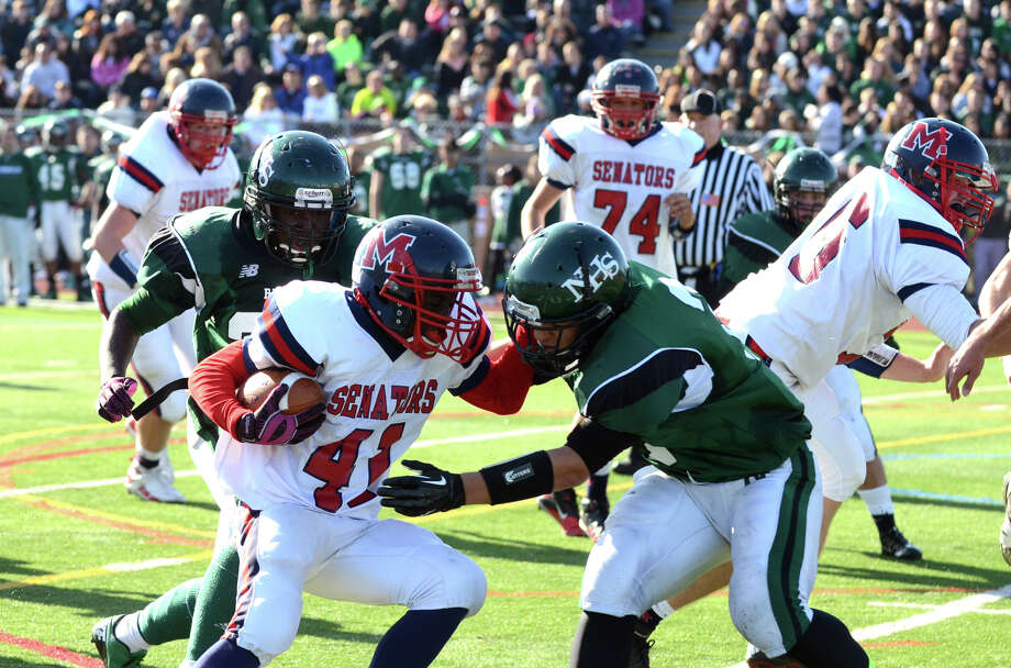 McMahon's Kentrell Snider (41) carries the ball as Norwalk's Andy Lovo (2) defends during the Thanksgiving Day football game at Norwalk High School on Thursday, Nov. 22, 2012. Photo: Amy Mortensen / Connecticut Post Freelance