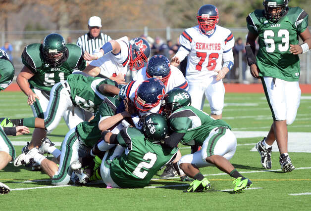 McMahon ball carrier Trevon Forney (4) is brought down by a slew of Norwalk defenders during the Thanksgiving Day football game at Norwalk High School on Thursday, Nov. 22, 2012. Photo: Amy Mortensen / Connecticut Post Freelance