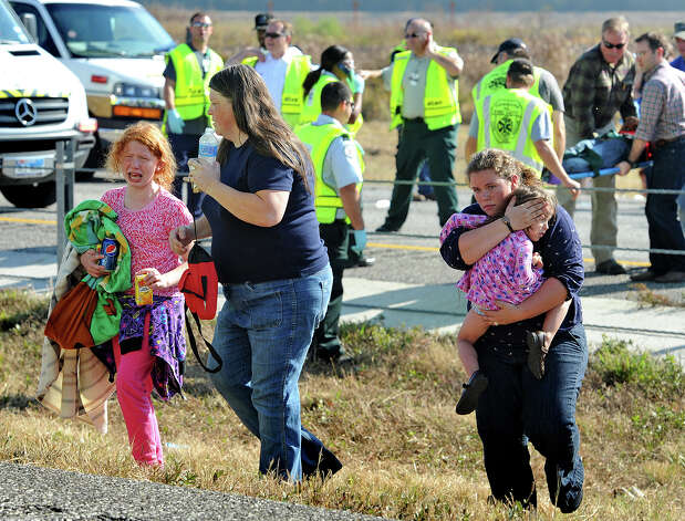 A family walks away from the scene of a massive wreck on Interstate 10 on Thanksgiving day. Heavy fog and speeders are said to be the causes of the wreck that involved more than 100 cars. Several tractor trailers, a thanker truck and bus were also involved in the pile up.  Photo taken Thursday, November 22, 2012 Guiseppe Barranco/The Enterprise Photo: Guiseppe Barranco, STAFF PHOTOGRAPHER / The Beaumont Enterprise