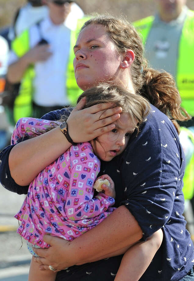 A woman carries a child away from the scene of a massive wreck on Interstate 10 on Thanksgiving day. Heavy fog and speeders are said to be the causes of the wreck that involved more than 100 cars. Several tractor trailers, a thanker truck and bus were also involved in the pile up. 
