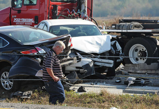 A man walks past a pile of cars from Thursday's accident on Interstate 10. Heavy fog and speeders are said to be the causes of the wreck that involved more than 100 cars. Several tractor trailers, a thanker truck and bus were also involved in the pile up.  Photo taken Thursday, November 22, 2012 Guiseppe Barranco/The Enterprise Photo: Guiseppe Barranco, STAFF PHOTOGRAPHER / The Beaumont Enterprise
