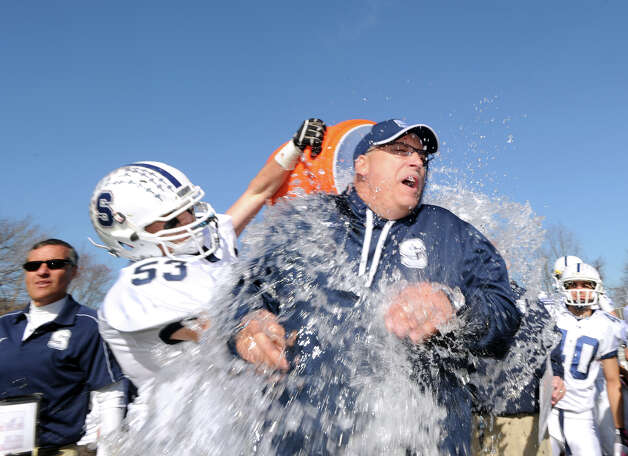 Brian Book # 53 of Staples douses his coach Marce Petroccio with Gatorade after Staples won the FCIAC championship 48-30 over Greenwich at Greenwich, Thursday afternoon, Nov. 22, 2012. At right looking on is Zach Speranza # 40 of Staples. Photo: Bob Luckey / Greenwich Time