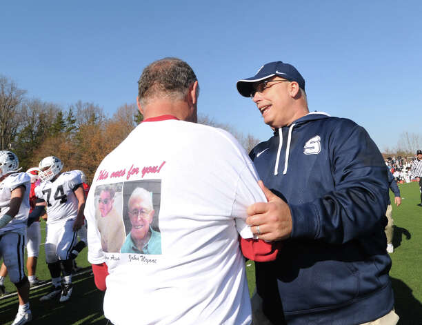 At left, Greenwich football coach Rich Albonizio, congratulates Staples football coach Marce Petroccio after Staples won the FCIAC championship, 48-30 at Greenwich, Thursday afternoon, Nov. 22, 2012. Photo: Bob Luckey / Greenwich Time