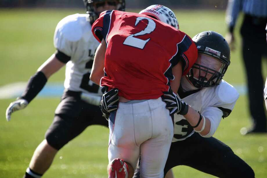 Mike Ross Connecticut Post freelance - Jonathan Law's #23 Timmy Speer applies a heavy hit on Foran High School's # 2 Nicholas Weissauer during first action on Thanksgiving football match-up on Thursday. Photo: Mike Ross / Connecticut Post Freelance