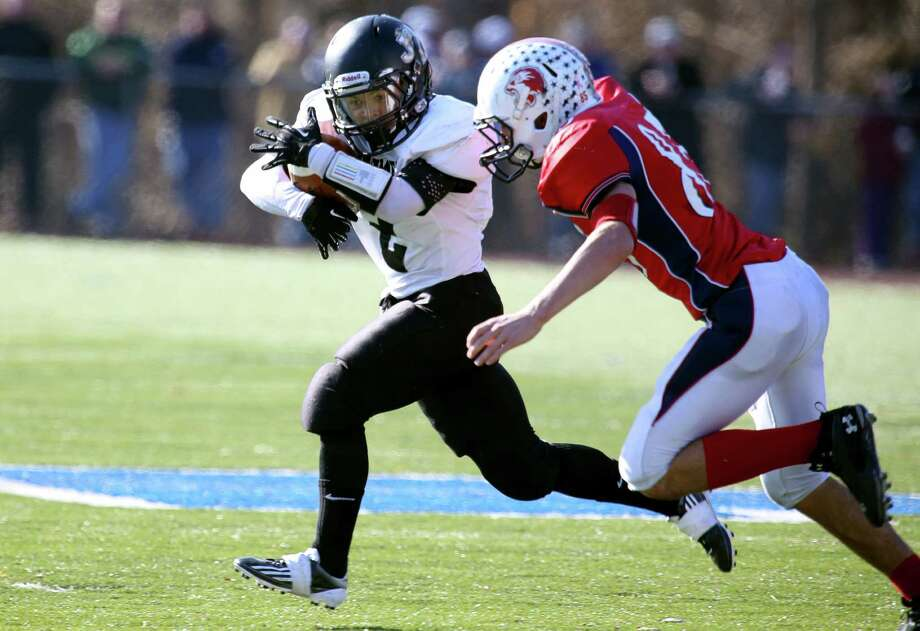 Mike Ross Connecticut Post freelance - Jonathan Law's #2 Daron Britt gains yardage on a first down run as Foran High School's # 85 Nicholas Griswwold gives chase during first action on Thanksgiving football match-up on Thursday morning. Photo: Mike Ross / Connecticut Post Freelance