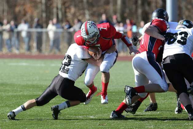 Mike Ross Connecticut Post freelance - Foran High School's # 7 quarterback Jake Kasuba scrambles for yardage as Jonathan Law High School's # 22 Timmy Maher makes the stop duirng Thursday Thanksgving football game. Photo: Mike Ross / Connecticut Post Freelance