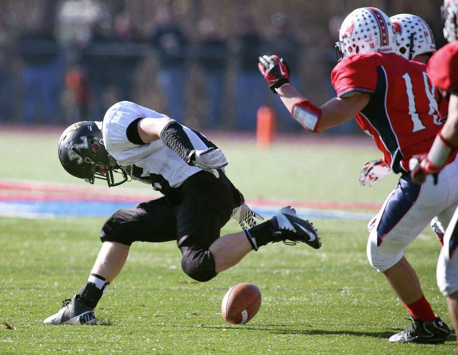 Mike Ross Connecticut Post freelance - Jonathan Law's #25  Danny Ziebell fumbles the ball during  first action on Thanksgiving football match-up against Foran High School. Foran would recover the ball on play. Photo: Mike Ross / Connecticut Post Freelance