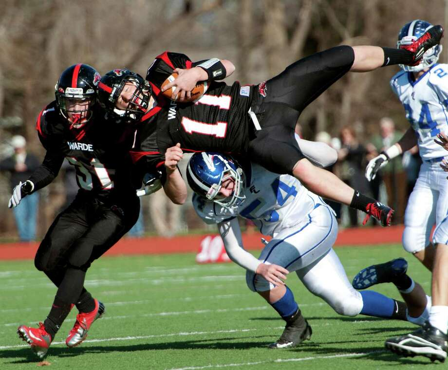 Fairfield Warde high school's Max Garrett gets upended by Fairfield Ludlowe high school's Benjamin Brzoski in the annual Thanksgiving Day football game played this year at Fairfield Warde high school, Fairfield, CT Thursday November 22nd, 2012. Photo: Mark Conrad / Connecticut Post Freelance