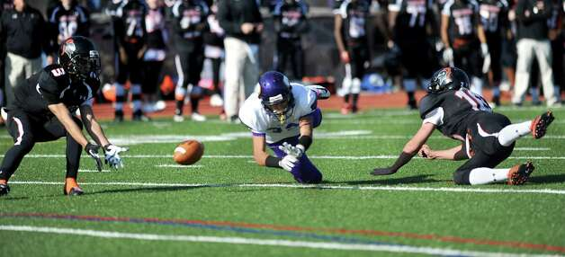 Westhill's Evan Skoparantzos, center, is flanked by Stamford's Jake Bivona, left, and Tyler Kane, right, as they all dive for a pass that fell incomplete during Thursday's game at Stamford High School on Thanksgiving day, November 22, 2012. Photo: Lindsay Niegelberg / Stamford Advocate