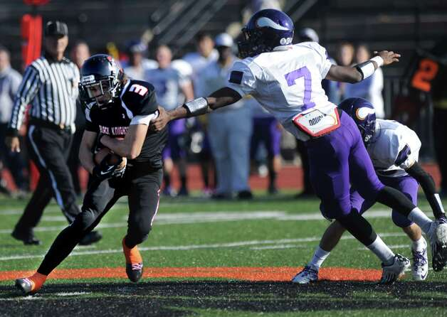 Westhill's Davell Cotterell reaches for Stamford ball-carrier Jake Bivona during a football game at Stamford High School on Thanksgiving day, Thursday, November 22, 2012. Photo: Lindsay Niegelberg / Stamford Advocate