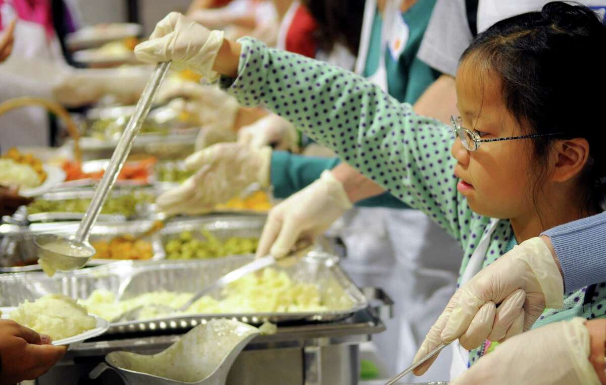 Volunteers, including Leping Ryan, 9, serve food during the 42nd annual Community Thanksgiving Day Feast at Christ and Holy Trinity Church in Westport on Thanksgiving day, Thursday, November 22, 2012.