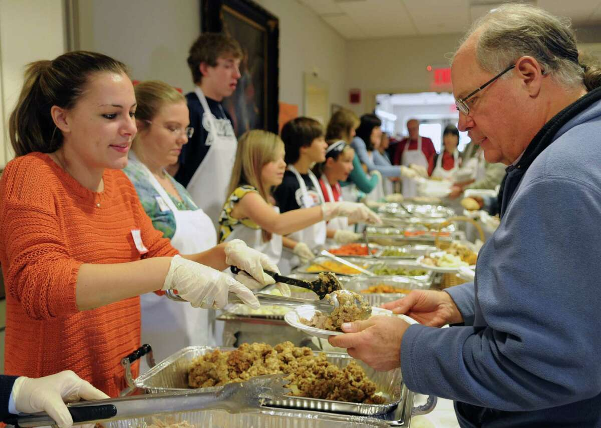 Volunteers, including Darby Searl, left, serve food during the 42nd annual Community Thanksgiving Day Feast at Christ and Holy Trinity Church in Westport on Thanksgiving day, Thursday, November 22, 2012.