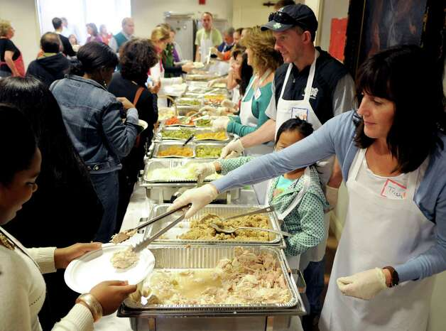 Volunteers serve food during the 42nd annual Community Thanksgiving Day Feast at Christ and Holy Trinity Church in Westport on Thanksgiving day, Thursday, November 22, 2012. Photo: Lindsay Niegelberg / Stamford Advocate