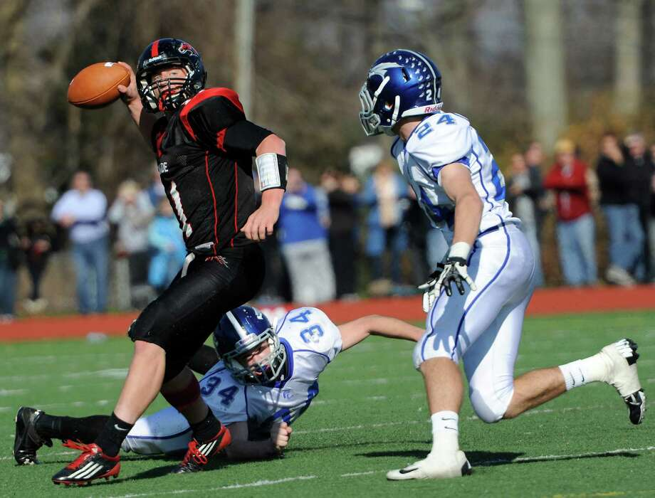 Fairfield Warde high school quarterback Max Garrett gets off a pass will under pressure from Fairfield Ludlowe high school's Jimmy Gasper (#34) and  Kyle Dammeyer (#24) in the annual Thanksgiving Day football game played this year at Fairfield Warde high school, Fairfield, CT Thursday November 22nd, 2012. Photo: Mark Conrad / Connecticut Post Freelance