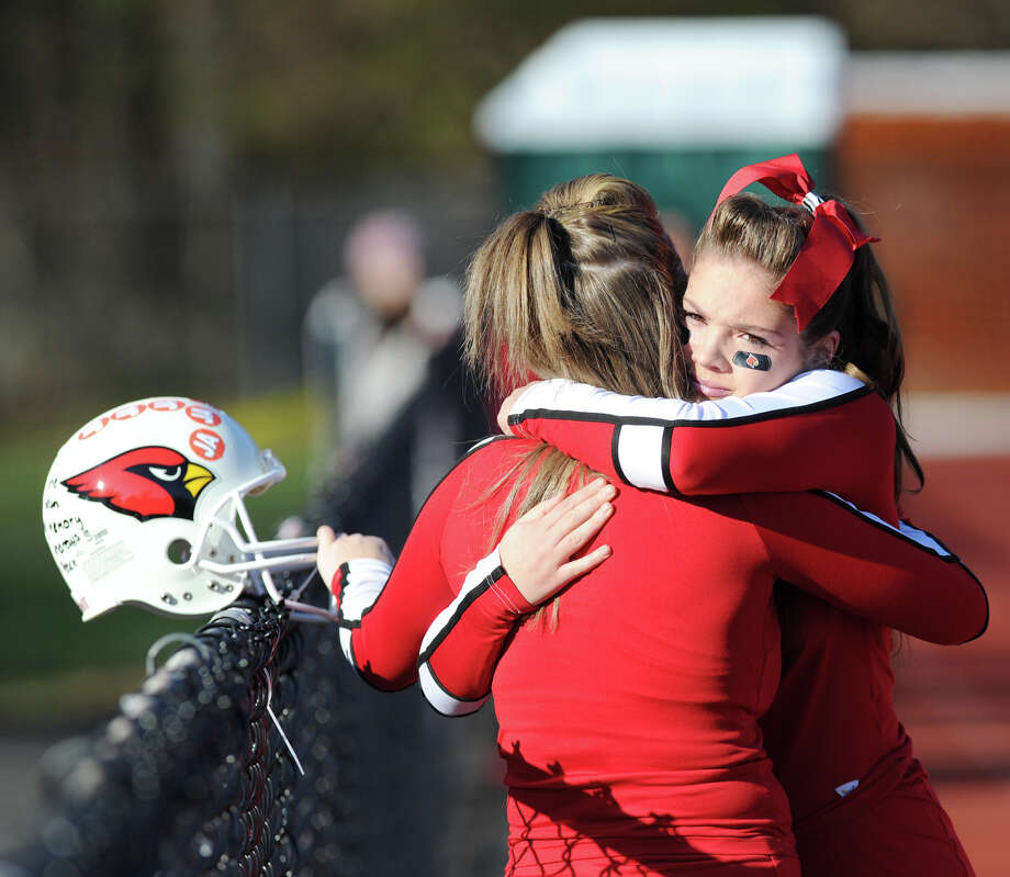 Greenwich cheerleader Mary Andrews gets a hug prior to the FCIAC championship football game between Staples High School and Greenwich High School at Greenwich, Thursday afternoon, Nov. 22, 2012. Andrews' father, John, recently past away and was honored prior to the game in which Staples defeated Greenwich 48-30 to win the championship. Photo: Bob Luckey / Greenwich Time
