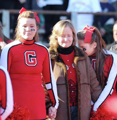 At center, Barbara Andrews of Greenwich is flanked by her daughters, Greenwich cheerleaders, Erin, left, and Mary, during a moment of silence for her husband and the girl's father, John Andrews, who recently past away, before the start of the FCIAC championship football game between Staples High School and Greenwich High School at Greenwich, Thursday afternoon, Nov. 22, 2012. Staples defeated Greenwich 48-30 to win the championship. Photo: Bob Luckey / Greenwich Time