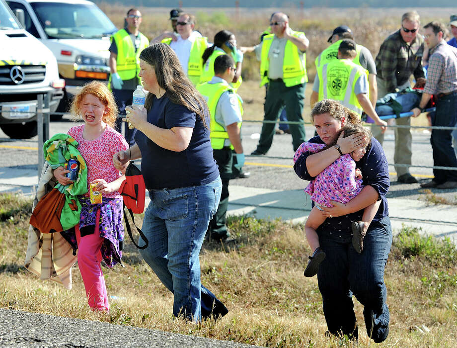 A family walks from the massive pile-up  accident on Interstate 10 in Southeast Texas Thursday Nov. 22, 2012.  The Texas Department of Public Safety says at least 35 people have been injured in a more than 50-vehicle pileup.    (AP Photo/The Beaumont Enterprise, Guiseppe Barranco) Photo: Guiseppe Barranco, Associated Press / The Beaumont Enterprise