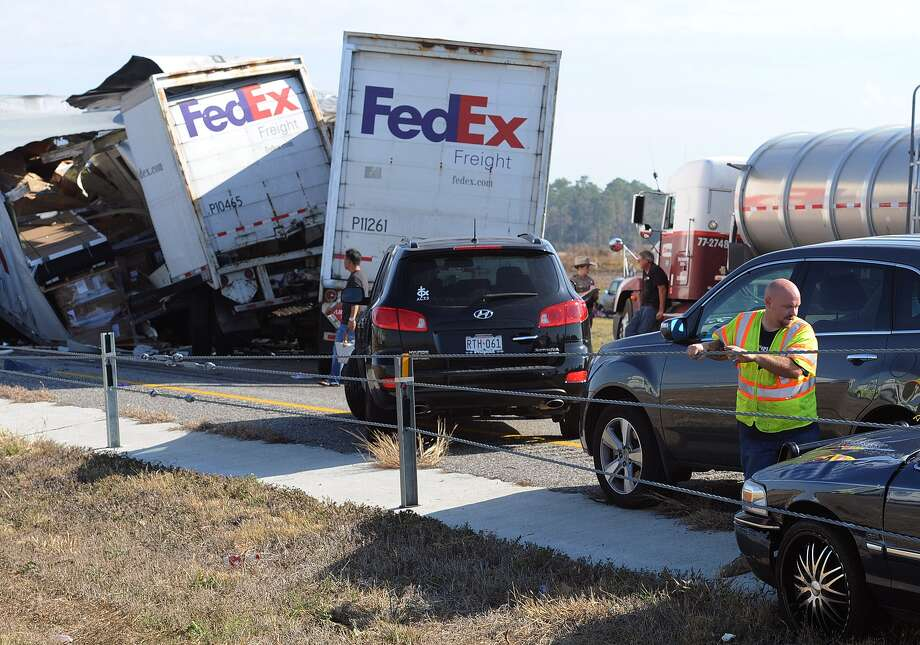 Cars and Trucks are piled on Interstate 10 in Southeast Texas Thursday Nov. 22, 2012.  The Texas Department of Public Safety says at least 35 people have been injured in a more than 50-vehicle pileup.    (AP Photo/The Beaumont Enterprise, Guiseppe Barranco) Photo: Guiseppe Barranco, Associated Press / The Beaumont Enterprise
