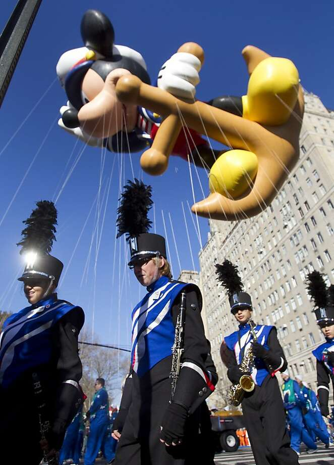 Members of the Oak Ridge High School Marching Band walk under a Mickey Mouse balloon as they make their way to the start of the Macy's Thanksgiving Day Parade Thursday, Nov. 22, 2012, in New York. Photo: Brett Coomer, Houston Chronicle