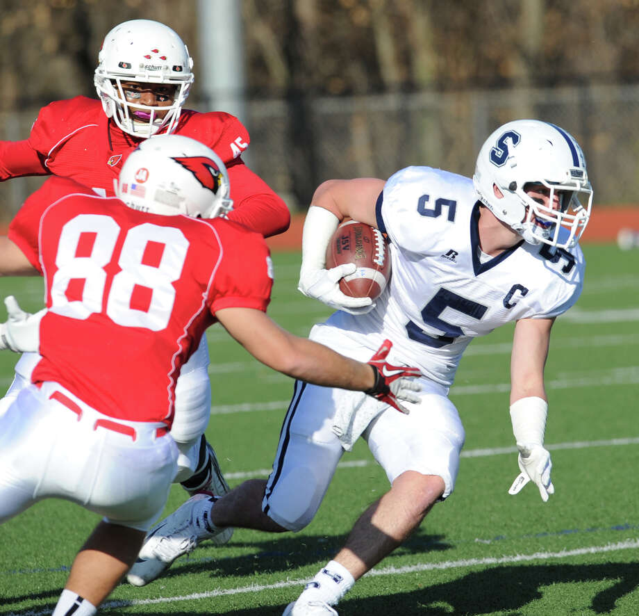 At right, Running back Nick Kelly # 5 of Staples gets past the arm of Greenwich defender Sam Latto during the first quarter of the FCIAC championship football game between Staples High School and Greenwich High School at Greenwich, Thursday afternoon, Nov. 22, 2012. Staples defeated Greenwich 48-30 to win the championship. Photo: Bob Luckey / Greenwich Time