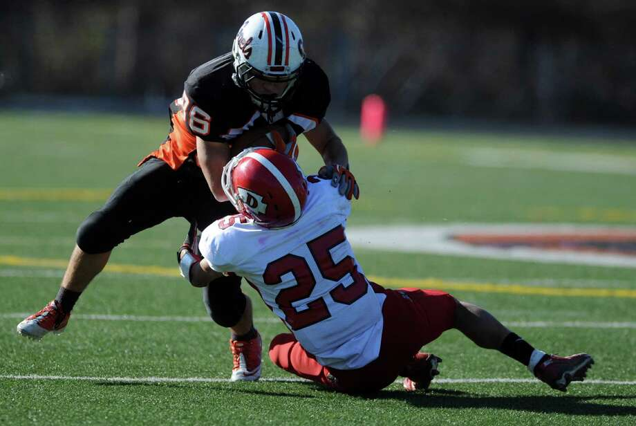 Shelton's Shane Corcoran throws off a tackle from Derby's Jordan LaRue during the Thanksgiving Day football game Thursday, Nov. 22, 2012 at Shelton High School. Photo: Autumn Driscoll / Connecticut Post