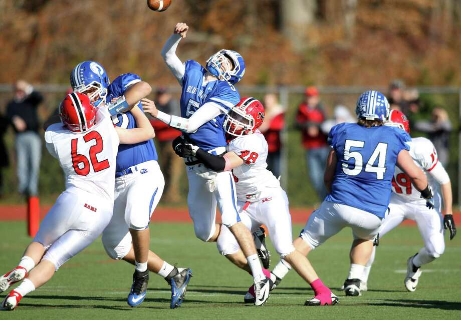Henry Baldwin of Darien is hit by New Canaan outside linebacker Alexander Dobbin during first quarter action in Darien. Baldwin, who was the MVP of the game, led Darien to a 36-23 win, Darien's first Turkey Day win in 11 years. Photo: J. Gregory Raymond / Stamford Advocate Freelance;  © J. Gregory Raymond