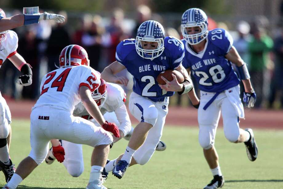 Darien High School running back Nick Mussicco scoots aroung left end for a short gain as he attempts to elude New Canaan defenders including Max Wilson (#24). Led by Henry Baldwin's play calling and direction, the Blue Wave dominated play, winning the annual Turkey Bowl game 36- 23, for the first time since 2001. Photo: J. Gregory Raymond / Stamford Advocate Freelance;  © J. Gregory Raymond