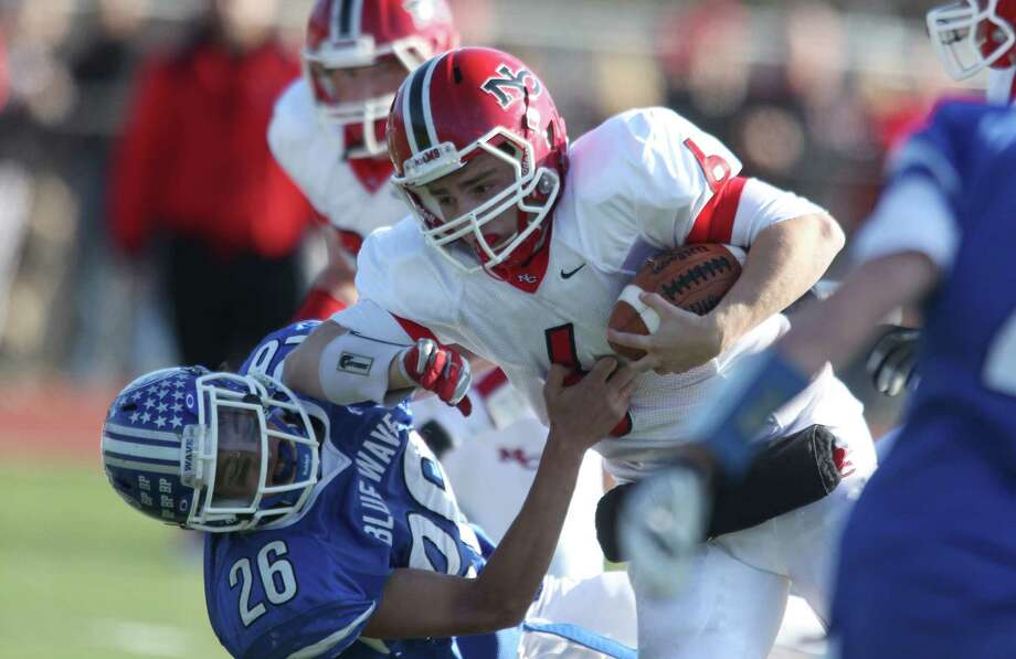New Canaan QB Teddy Bossidy bowls over Darien defender PeterGesualdi for a short gain during FCIAC action in Darien. The Blue Wave, which fell behind 14-0 would soon dominate play on both sides of the ball to win 36-23. Photo: J. Gregory Raymond / Stamford Advocate Freelance;  © J. Gregory Raymond
