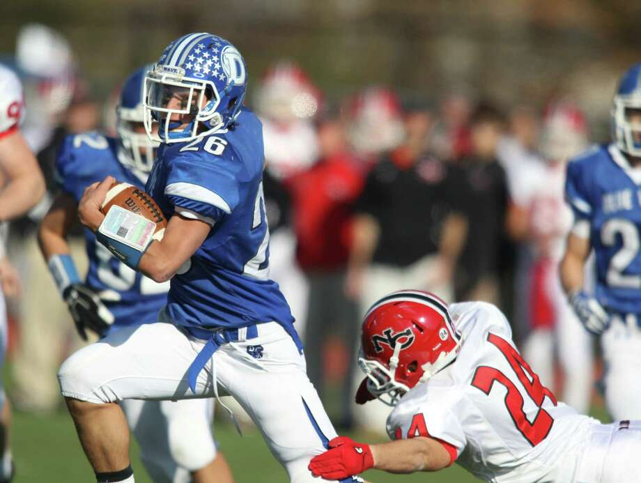 Darien High School running back Peter Gesualdi cuts back against the grain for a sizeable gain as New Canaan defender Max Wilson attempts to tackle. Led by an MVP performance by QB Henry Baldwin, Darien won convincingly, 36-23. Photo: J. Gregory Raymond / Stamford Advocate Freelance;  © J. Gregory Raymond