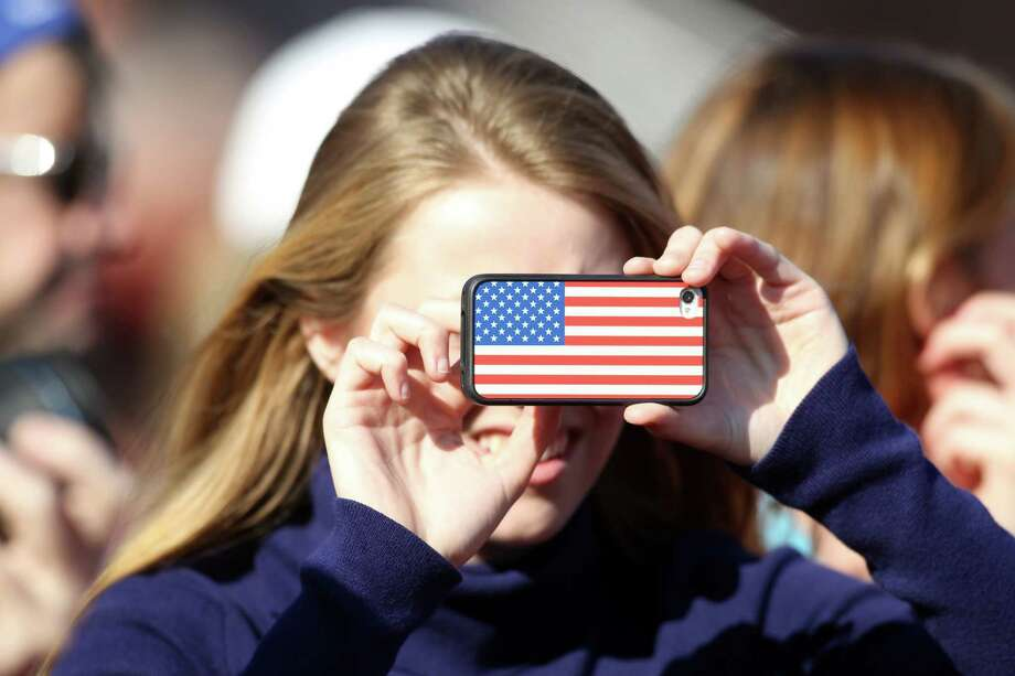 A young Darien High School fan takes a photo on her i phone during the annual Turkey Day game against New Canaan on Thursday. Darien won the game, 36-23. Photo: J. Gregory Raymond / Stamford Advocate Freelance;  © J. Gregory Raymond