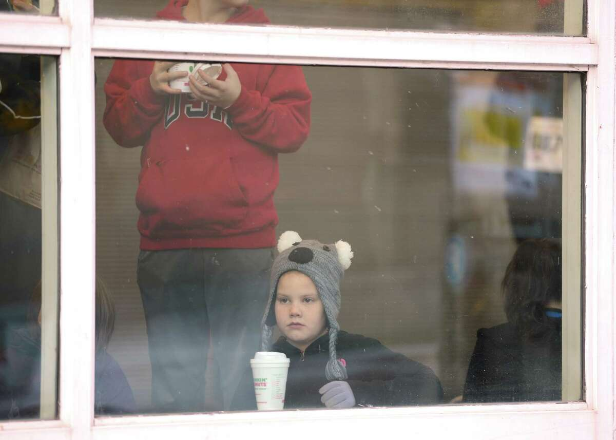 A young person watches through the window of the Troy Atrium as runners warm up the 65th running of the Troy Turkey Trot in Troy, N.Y. Nov 22, 2012. (Skip Dickstein/Times Union)