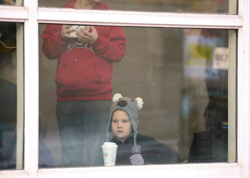 A young person watches through the window of the Troy Atrium as runners warm up the 65th running of
