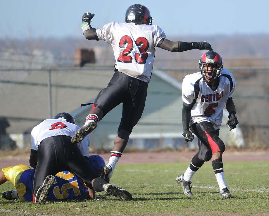 From left; Central's Johan Mann, Andrew Louis, and Mykel Morris, celebrate a tackle of Harding's D.J. Smith during their annual Thanksgiving Day game at Harding High School in Bridgeport on Sunday, November 22, 2012. Photo: Brian A. Pounds / Connecticut Post