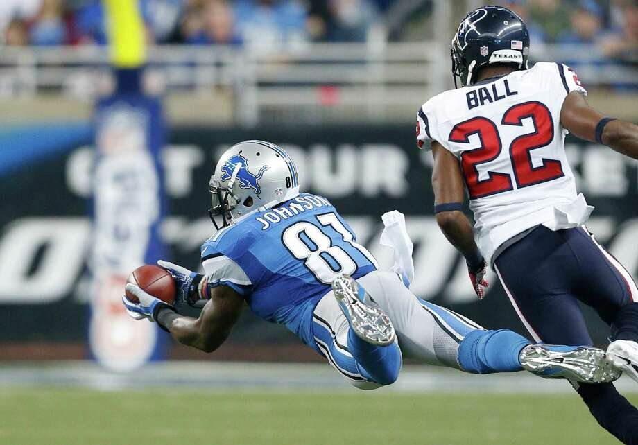 Detroit Lions wide receiver Calvin Johnson (81), defended by Houston Texans defensive back Alan Ball (22) makes a catch during the first quarter of an NFL football game at Ford Field in Detroit, Thursday, Nov. 22, 2012. (AP Photo/Rick Osentoski) Photo: Rick Osentoski, Associated Press / FR170444 AP